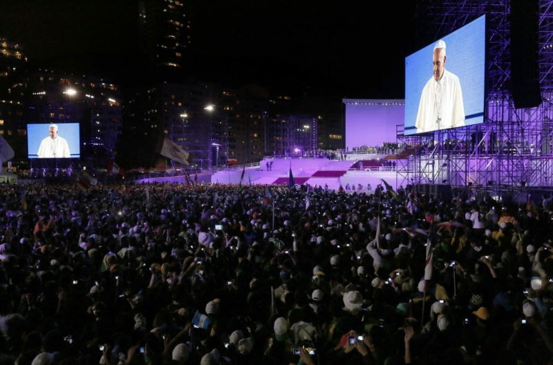 26jul2013-papa-francisco-e-visto-em-telao-durante-a-cerimonia-de-recepcao-do-pontifice-na-jornada-mundial-da-juventude-em-copacabana-no-rio-de-janeiro-1374838909930_1024x682